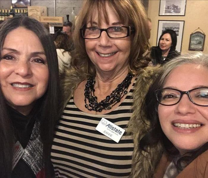 Three ladies standing together at a networking event