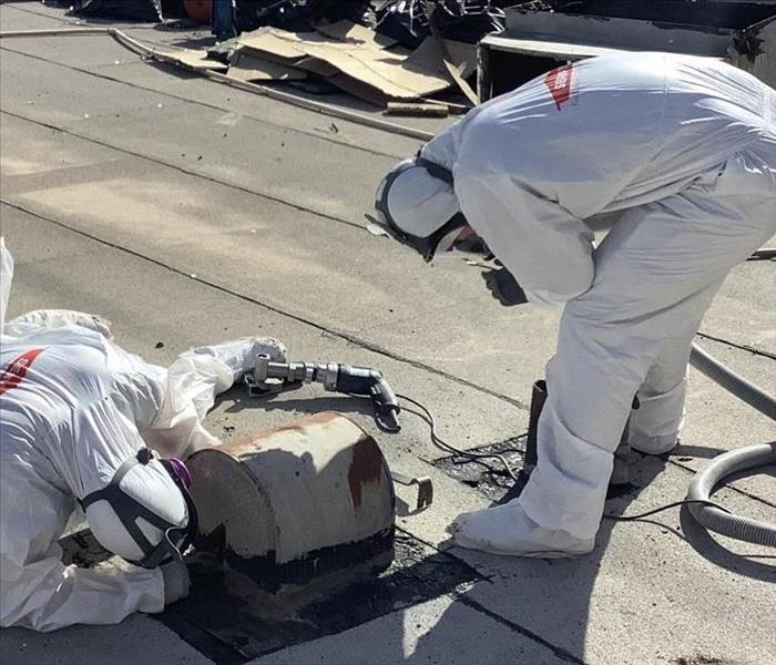 SERVPRO technicians in protective clothing on roof