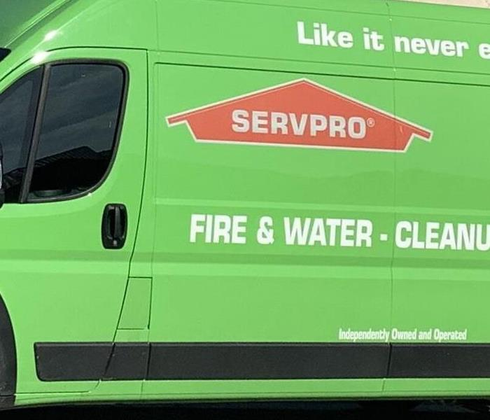 A SERVPRO vehicle parked in front of a home.